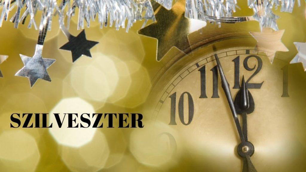 karácsonyfadíszek alatt elmosódott óralap, szilveszter felirattal