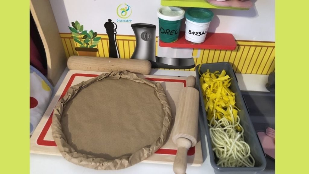 játékkonyhán játékpizza fotózva, mellette reszelt sajt, sodrófa, felette polcon fűszerek