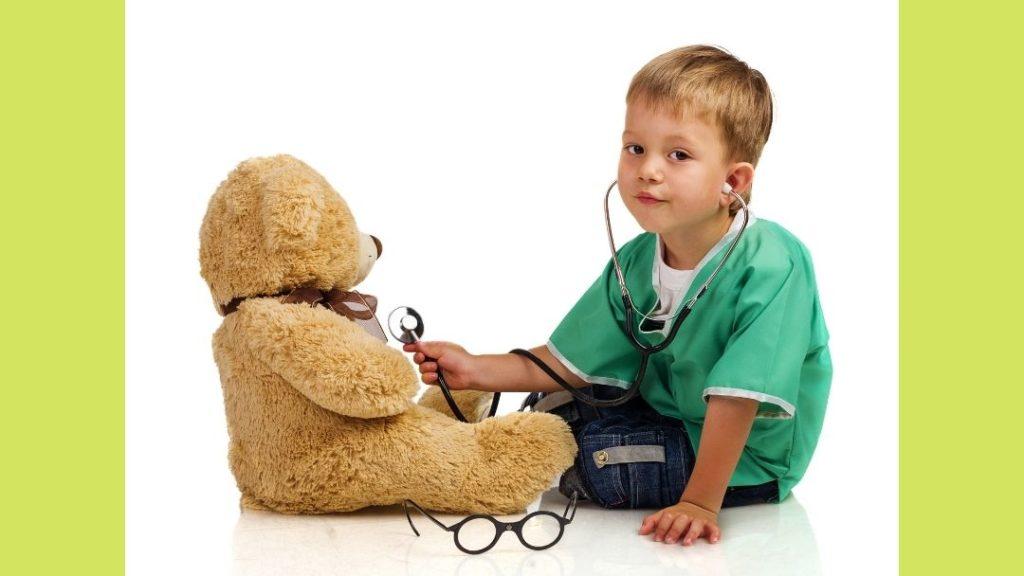 kisfiú plüssmedvét hallgat játék sztetoszkóppal