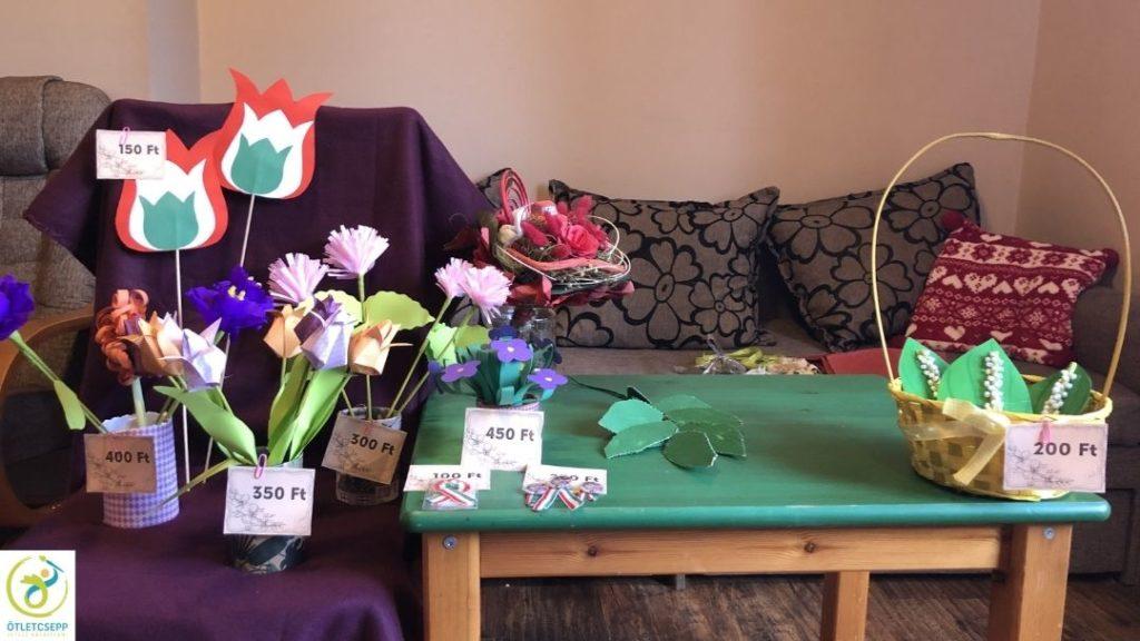 szék leterítve pléddel, rajta sokféle papír virág fajtánként szétválogatva, mellette zöld kis asztalon cserepes papírnövény, papír gyöngyvirág kosárban, egy örökcsokor
