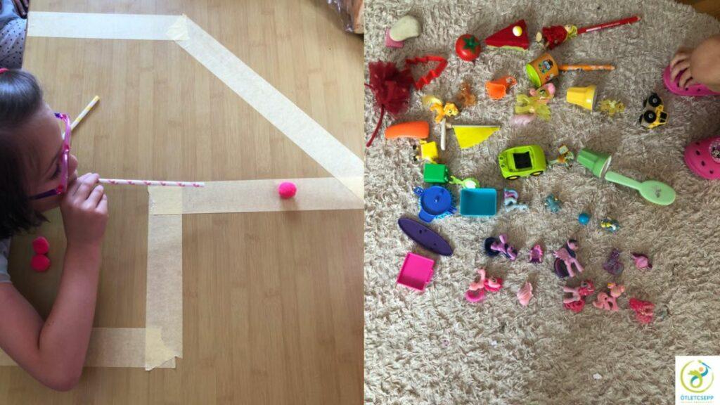 kislány szívószállal pompont fúj végig egy kijelölt pályán, mellette szőnyegen színes játékokból szivárvány