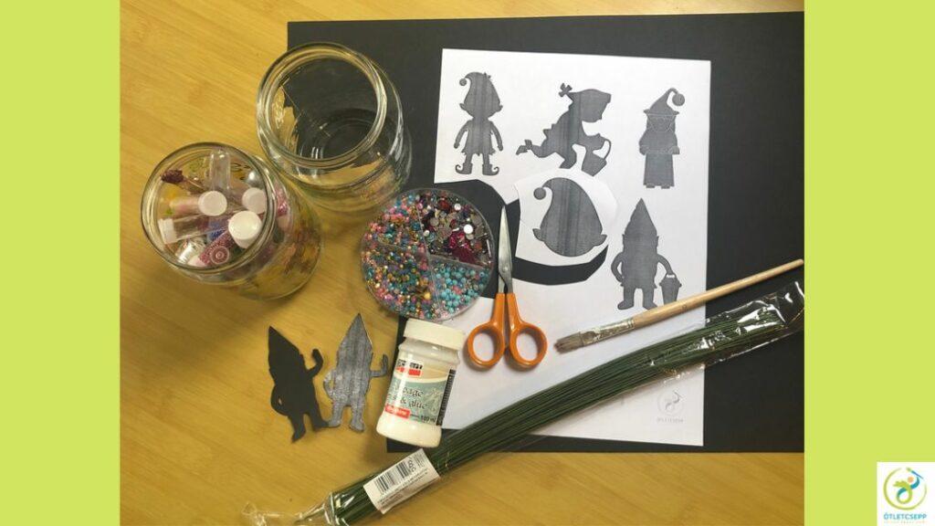 lámpás kellékei: üres befőttesüveg, fekete karton, decoupage ragasztó, ecset, csillámpor, drót, gyöngyök, led mécses, sablon, hegyes kisolló vagy sniccer